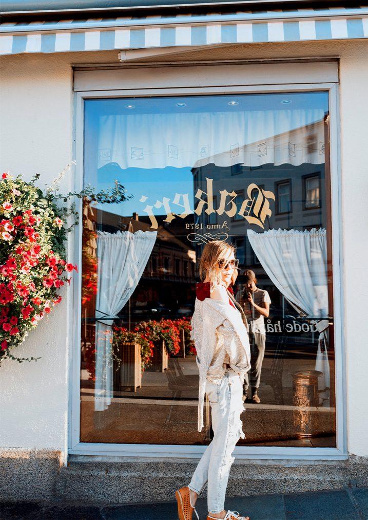 millennial woman standing next to bakery window