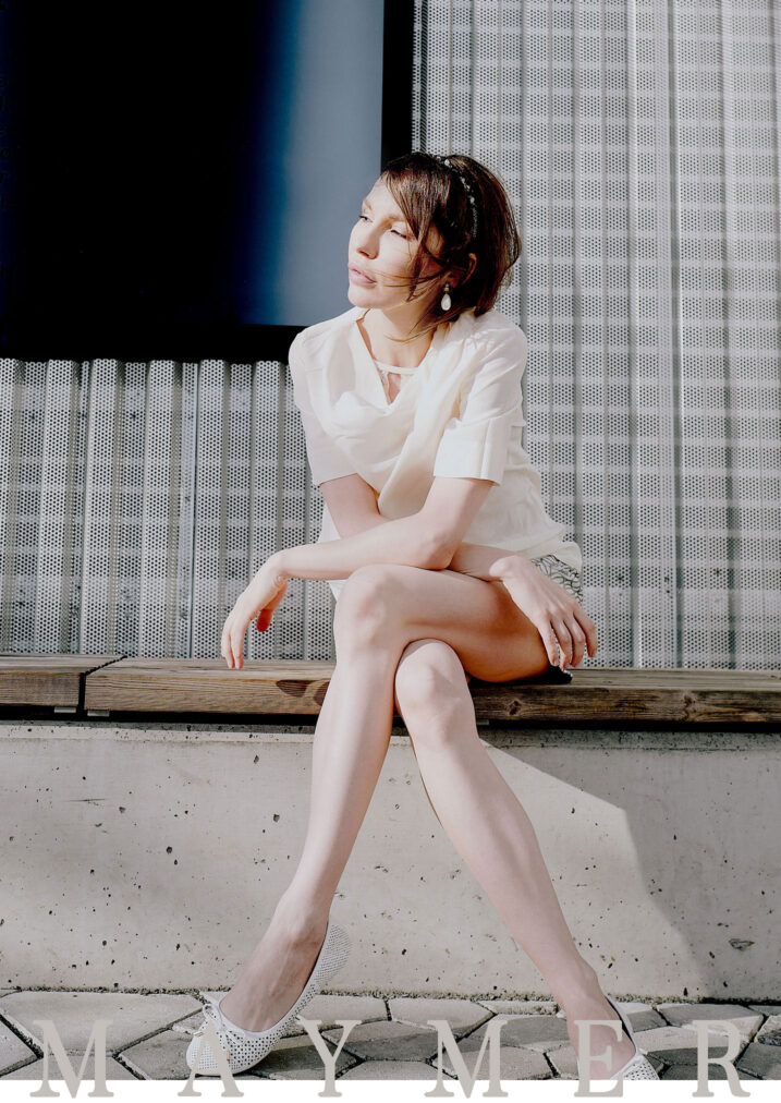 martha may sitting on the bench wearing white silk shirt