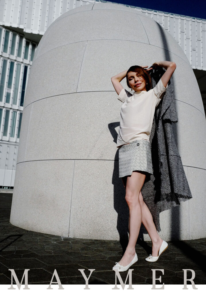 martha may holding grey sweater and posing in grey mini skirt and silk shirt