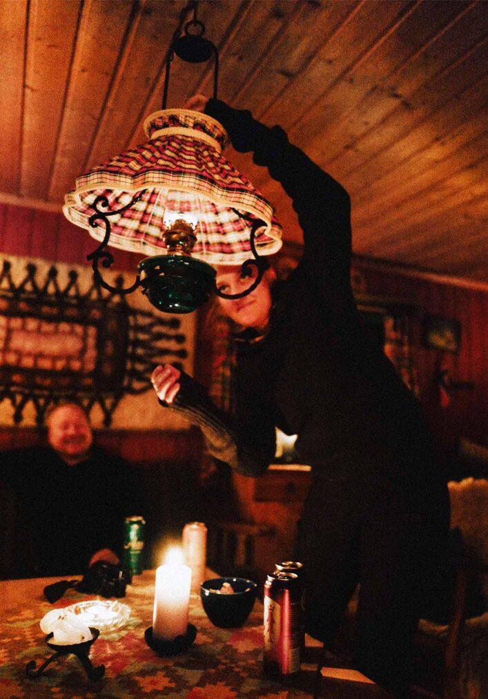 hytteliv girl fixing oil lamp at hytta near oslo