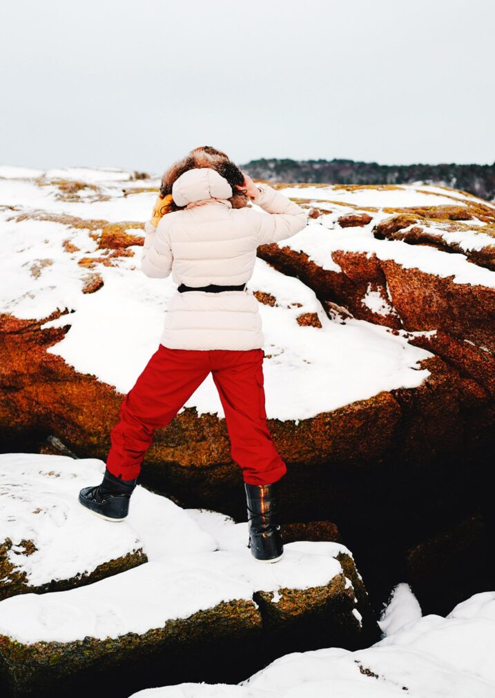 martha may climbing rocks covered in snow