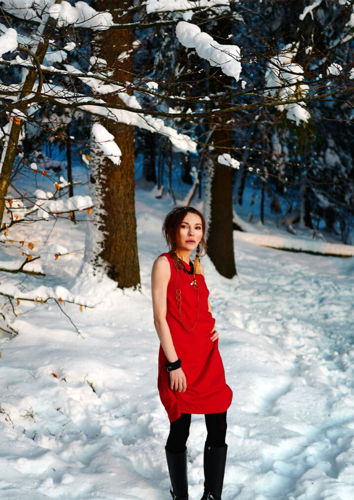 martha may in a red cocktail dress in the winter forest oslo norway