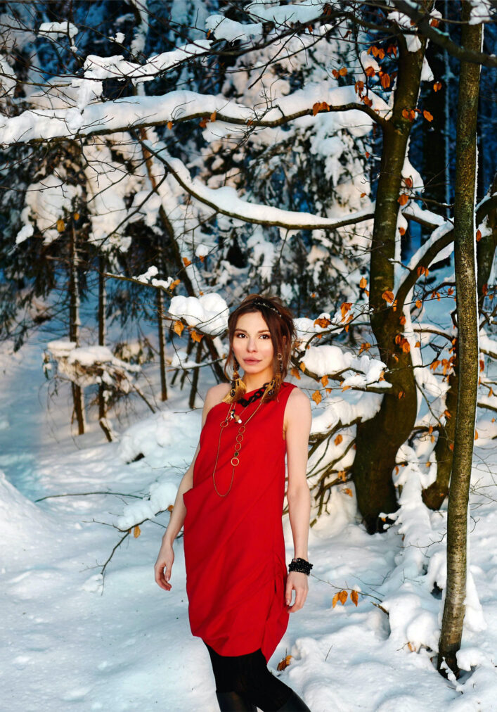 martha may standing in a red cocktail dress in a winter forest